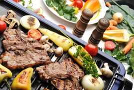 Barbecue, prepared beef meat and different vegetables and mushrooms on